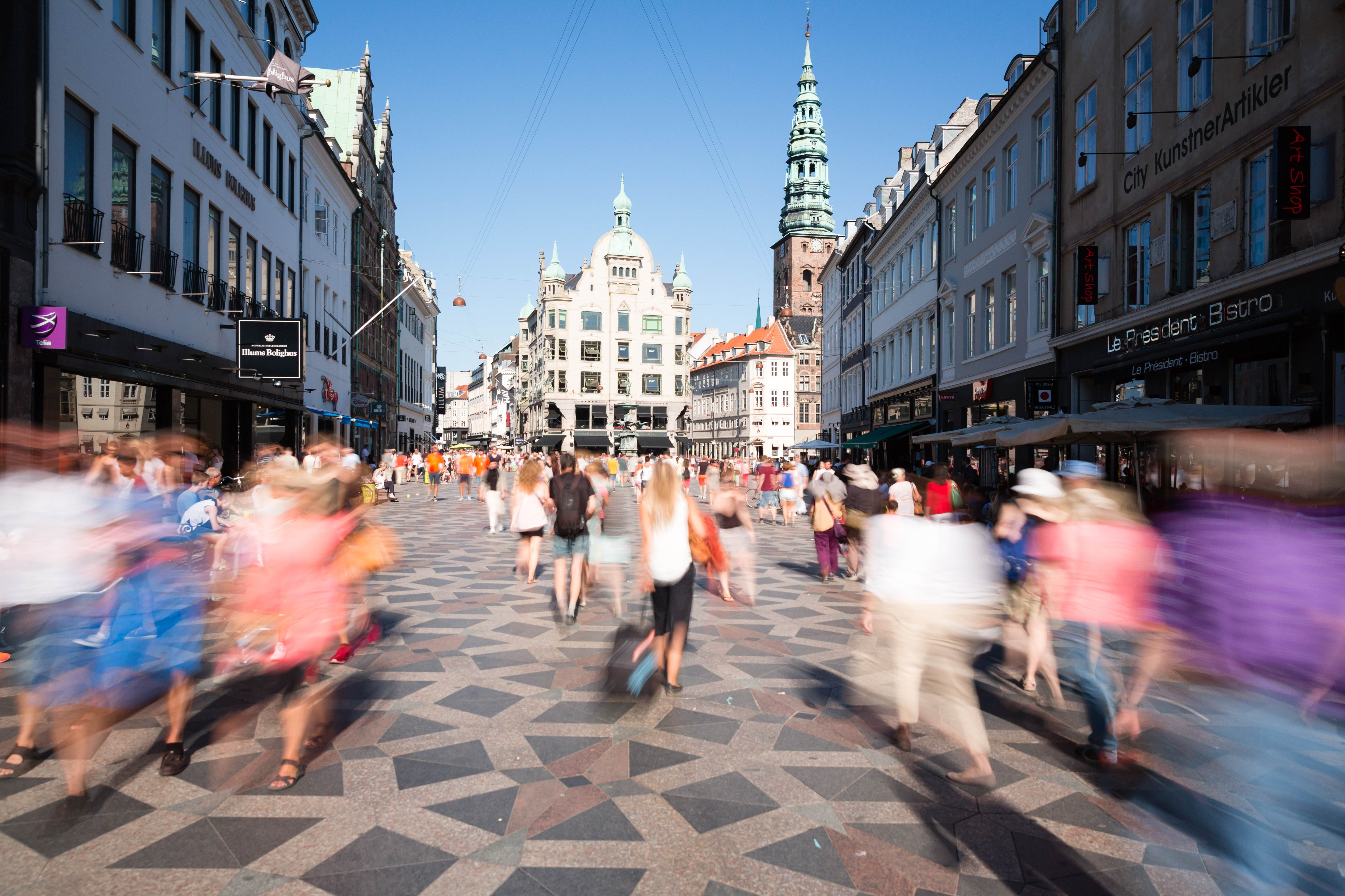 COPENHAGEN, DENMARK - JULY 9, 2014: Tourists and local citizens stroll through the central pedestrian area of the Danish capital of Copenhagen as local restaurants and merchants prepare for the peak tourism season in july and august.